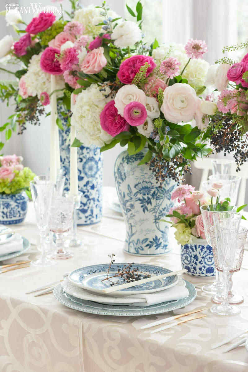 blue and beige asian table setting with large floral vases