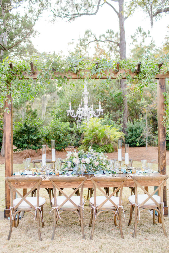 Rustic outdoor wedding table with hanging greenery