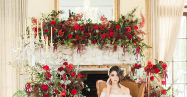 bride surrounded by red roses